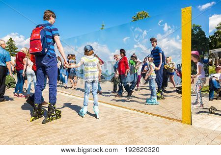 Samara Russia - May 12 2017: People near the giant stainless steel mirror at the city park in summer sunny day