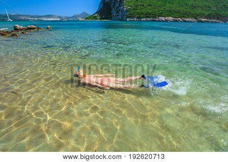 Young female in orange bikini snorkeling in beautiful clear waters of famous Voidokilia Beach in Peloponnese, Greece. Woman snorkeler swims in summer season. Water sports activities and leisure.