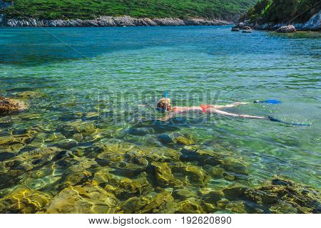 Young caucasian female bikini snorkeling in beautiful crystal waters of famous Voidokilia Beach in Peloponnese, Greece. Woman snorkeler swims over the rocks. Water sports activities. Summer season.