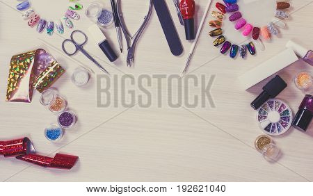 Manicure set on a wooden table. Nail files, paints, scissors, nail accessories on pink bright background