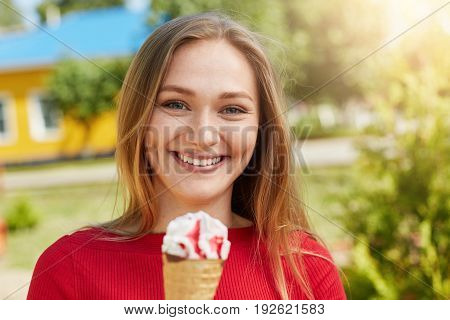 Smiling Attractive Young Female With Dimples On Her Cheeks Having Fun And Good Mood While Eatting Ic