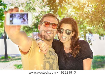 Portrait of a young attractive tourist couple using a smartphone to take a selfie picture having emotional fun together while visiting a touristic destination city. Love and technology lifestyle