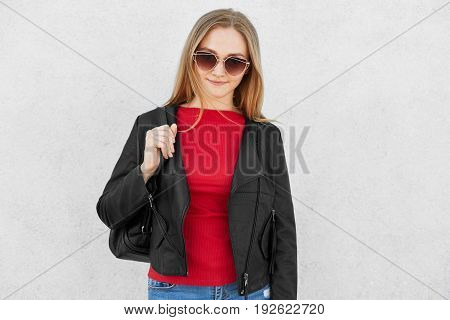 Fashionable Fair-haired Woman Wearing Trendy Sunglasses, Red Sweater And Black Leather Jacket Holdin