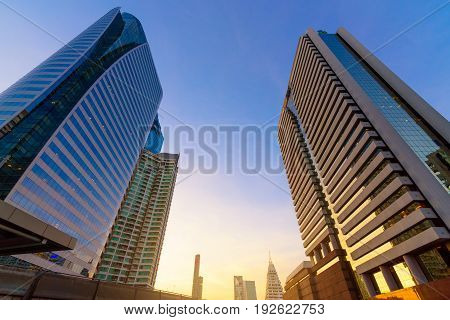 Photo of commercial office buildings exterior. Night view at bottom skyscrapers with flare light effect long exposur in Bangkok.