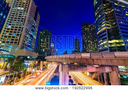Photo of commercial office buildings exterior. Night view at bottom skyscrapers with light of traffic rush long exposur in Bangkok.