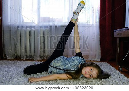girl doing exercises at home on the carpet
