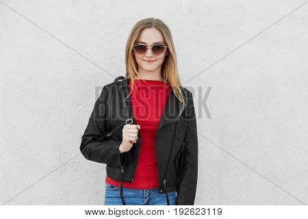Portrait Of Fashionable Young Lady In Big Trendy Sunglasses, Red Sweater, Jeans And Leather Coat Hol
