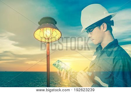 Double exposure of Engineer or Technician man in working shirt working with tablet in lamp and sea background for electricity industry concept.