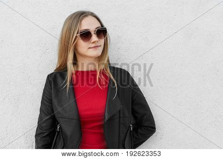 Sexy Blonde Female In Sunglasses And Black Leather Coat Standing Against White Concrete Wall With Bl