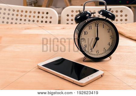 smartphone and black retro alarm clock times at 7 o'clock morning on wooden table selective focus copy space vintage color tone