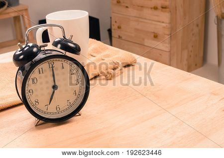 white coffee cup and black retro alarm clock times at 7 o'clock morning on wooden table selective focus copy space vintage color tone