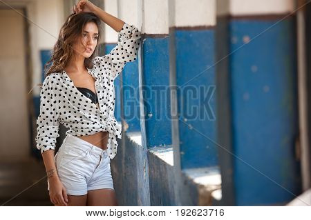 Beautiful girl with white shirt and white shorts posing in old hall with columns blue painted. Attractive long hair brunette, side view against ancient pillars.Dark hair young woman with gorgeous eyes