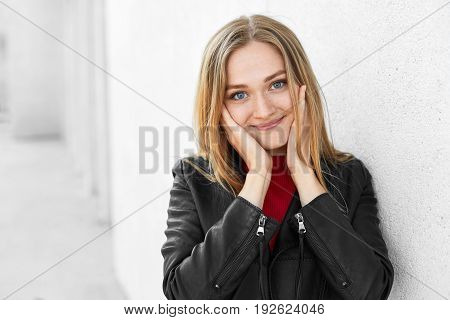Adorable Woman With Straight Fair Hair, Warm Blue Eyes And Gentle Smile Holding Her Delicate Hands O