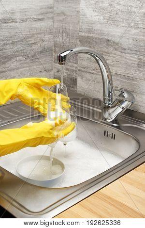 Hands In Gloves Washing Drinking Glass Under Running Tap Water