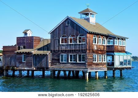 Rustic Cape Cod style wooden building on a pier taken in a bay