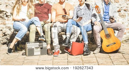 Group of multicultural friends using smartphone on urban background - Technology addiction concept in youth lifestyle disinterested to each other - Always connected people on modern mobile smart phone