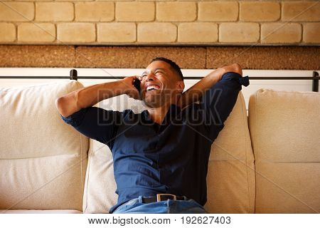 Relaxed Young Black Man Talking On Mobile Phone With Hand Behind His Head