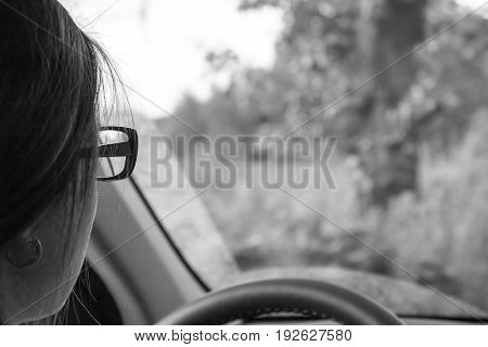 Girl with glasses at the wheel of the car. View from behind the seated driver