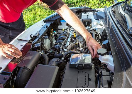 A man checks the engine by opening the car's hood
