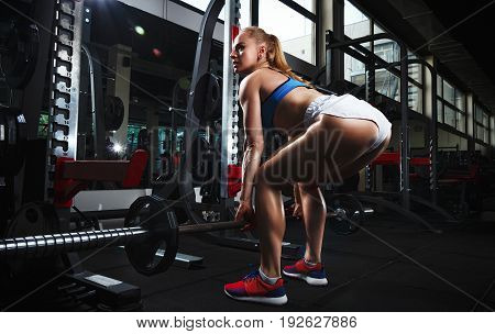 Fitness Young Sweaty Girl With Sports Body In The Gym Doing Squat With Barbell