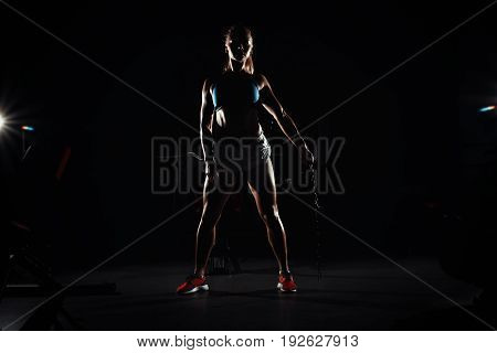 Fitness Young Sweaty Girl With A Sports Body In The Gym Sexually Posing With A Chain. Silhouetted In