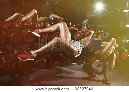 Fitness Young Sweaty Girl With A Sports Body In The Gym Sexually Lies On A Dumbbell