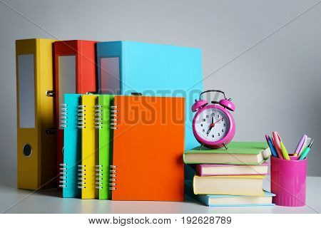 Colorful office folders with books notebooks and alarm clock