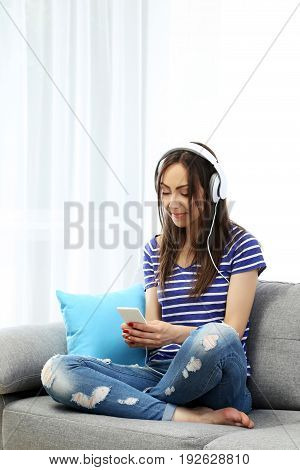 Young woman sitting on sofa and listening music with headphones
