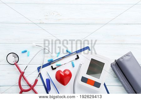 White Electric Tonometer With Stethoscope On Wooden Table