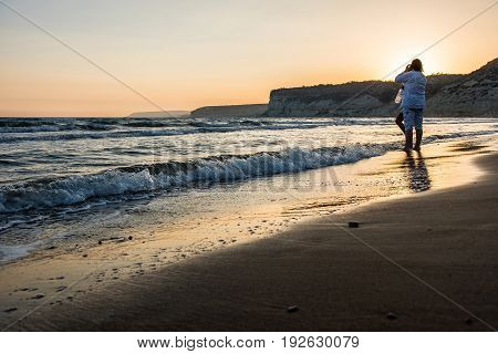 Two Women Enjoying The Sunset On A Beach