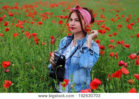a young girl with retro camera in a field of poppies.