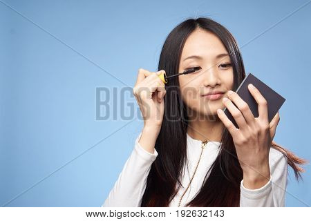 Woman paints eyelashes, mascara, woman on blue background.
