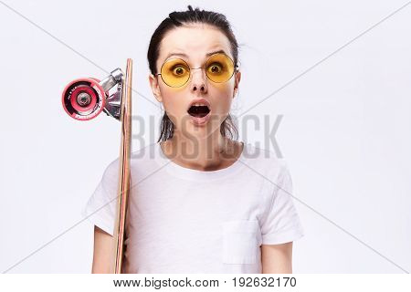 Sport, woman with glasses, woman with skateboard on a light background.
