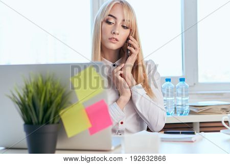 Business woman talking on the phone, business woman looking at the laptop.