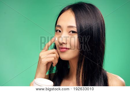 Woman with cream, woman applying cream on face, face care, face cream, woman on green background.