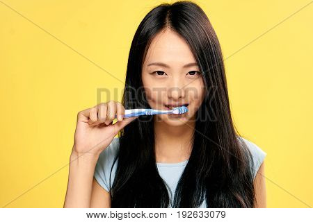 Teeth care, woman brushes teeth, woman on yellow background.
