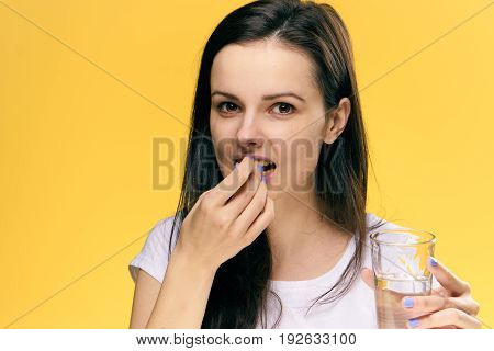 Health, woman sick, woman with pill, pill, glass of water, woman on yellow background.