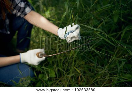 Woman in working gloves, woman mowing grass, woman pulling grass, season, summer, summer residence.