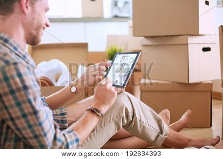 Young couple moving in new home.Sitting on floor and relaxing after unpacking.Looking something on laptop