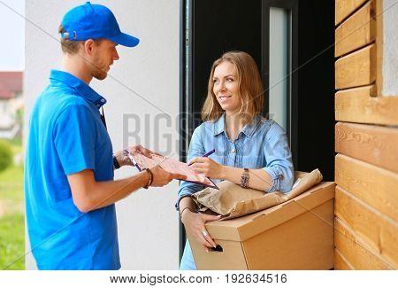 Smiling delivery man in blue uniform delivering parcel box to recipient - courier service concept
