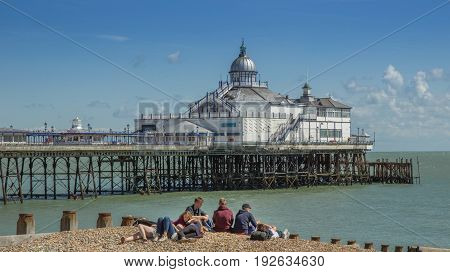 Eastbourne Sussex England - August 8 2014: Eastbourne Pier with young people in the foreground on the beach.