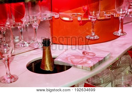 Serving wine glasses and a bottle of champagne in the car in red carrying candles .