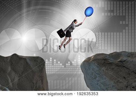 Businesswoman flying holding balloon