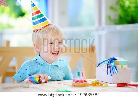 Cute Little Boy Having Fun And Celebrate Birthday Party With Colorful Decoration And Cake