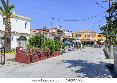 SIDARI, GREECE - MAY 24: A typical colorful street in a seaside town awaits tourists on a sunny day on May 24, 2017 in Sidari, Corfu island in Greece.