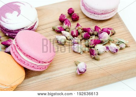 French Delicious Pink Color Macarons Cookies And Small Roses On Wood Desk.
