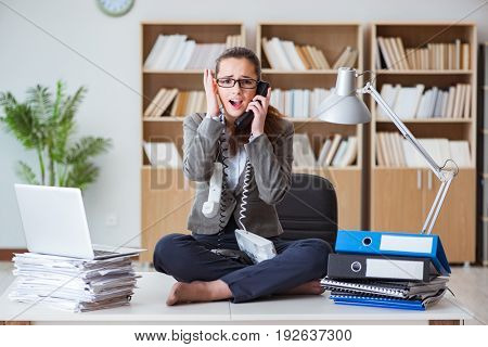 Busy angry businesswoman sitting on the desk in office