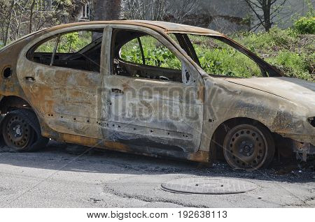 Burned car parked on the street side view - Close up photo of a burned out car