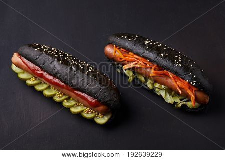 hot dogs in black buns over dark background