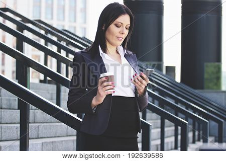 Staying Connected. Portrait Of Beautiful Young Business Woman Looking At Smart Phone While Drinking